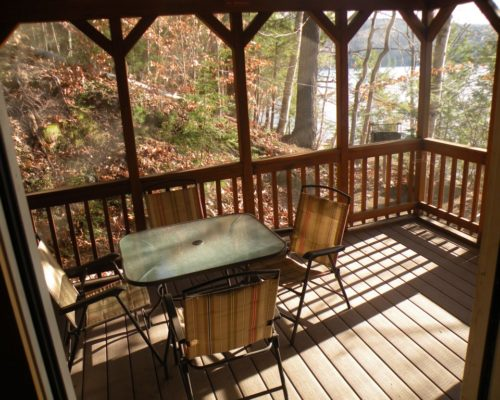 sun porch at cabin with dining table and chairs