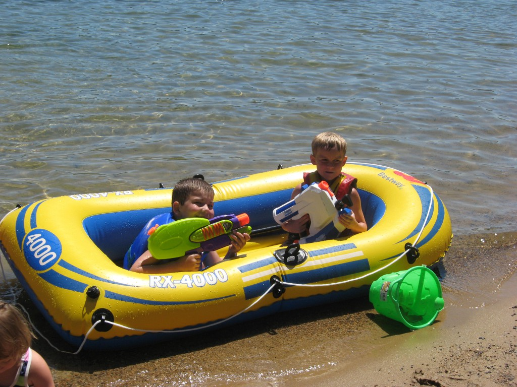 two young boys with water guns in inflatable raft